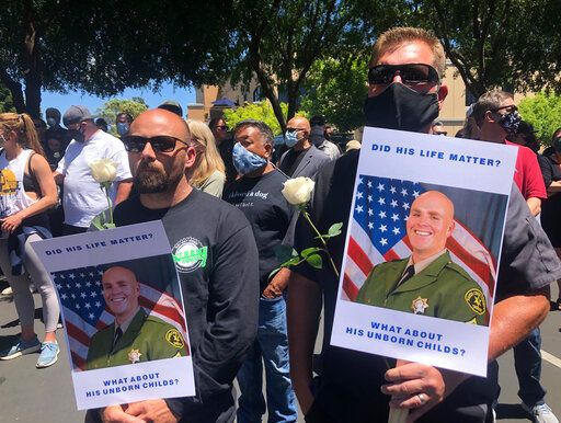 Matthew Rose, left, and Michael Carr, of Santa Cruz County hold posters of slain Sgt. Damon Gutzwiller, as they join others outside the Santa Cruz County Sheriff-Coroner's Office to pay their respects in Santa Cruz, Calif., Sunday, June 7, 2020. Santa Cruz County Sheriff's Sgt. Gutzwiller, 38, was shot and killed in Ben Lomond, an unincorporated area near Santa Cruz. Sheriff Jim Hart said the suspect, Steven Carrillo, was shot during the arrest and is being treated at a hospital.