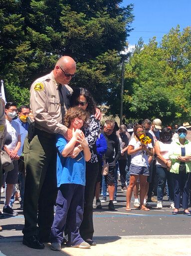 CORRECTS THAT THE WOMAN AND THE CHILD SHOWN ARE THE WIFE AND SON OF SHERIFF JIM HART, NOT THE WIFE AND SON OF DECEASED DEPUTY SGT. DAMON GUTZWILLER - Santa Cruz Sheriff Jim Hart stands next to Hart's wife and child, as more than a thousand people gather outside the Santa Cruz County Sheriff-Coroner's Office to pay their respects to fallen Sgt. Damon Gutzwiller in Santa Cruz, Calif., Sunday, June 7, 2020. Santa Cruz County Sheriff Sgt. Damon Gutzwiller, 38, was shot and killed in Ben Lomond, an unincorporated area near Santa Cruz.