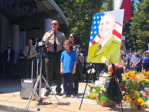 CORRECTS THAT THE WOMAN AND THE CHILD SHOWN ARE THE WIFE AND CHILD OF SHERIFF JIM HART, NOT THE WIFE AND CHILD OF DECEASED DEPUTY SGT. DAMON GUTZWILLER - Santa Cruz Sheriff Jim Hart stands next to Hart's wife and child and  a photo of fallen Sgt. Damon Gutzwiller, as more than a thousand people gather outside the Santa Cruz County Sheriff-Coroner's Office to pay their respects in Santa Cruz, Calif., Sunday, June 7, 2020. Santa Cruz County Sheriff Sgt. Damon Gutzwiller, 38, was shot and killed in Ben Lomond, an unincorporated area near Santa Cruz.