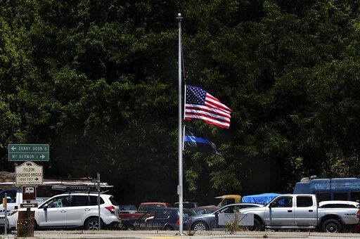The American Flag flies at half-staff along with the Thin Blue Line Flag in downtown Felton, Calif., Monday, June 8, 2020, a few miles from where Santa Cruz County Sheriff's Sgt. Damon Gutzwiller was fatally shot on Saturday. The Thin Blue Line flag is flown as a way to pay tribute to a peace officer killed in the line of duty. An active-duty U.S. Air Force sergeant accused of killing a Northern California sheriff's deputy in an ambush-style attack was a leader for a military base's elite security force, officials said Monday. (Shmuel Thaler/Santa Cruz Sentinel via AP)