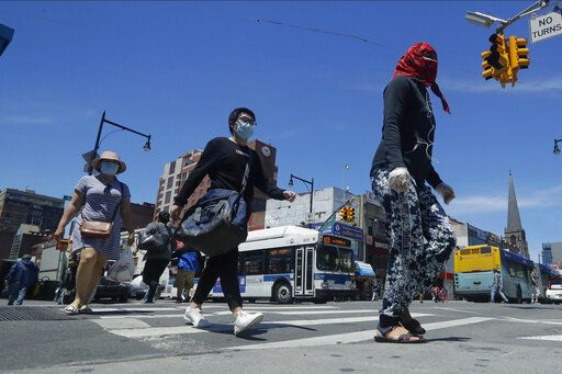 Pedestrians wear face coverings and protective masks as they cross Mains street, Monday, June 8, 2020, in the Flushing section of the Queens borough of New York. After three bleak months, New York City will try to turn a page when it begins reopening Monday after getting hit first by the coronavirus, then an outpouring of rage over racism and police brutality.