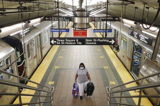 A commuters walks on a nearly empty subway platform in New York, Monday, June 8, 2020. After three months of a coronavirus crisis followed by protests and unrest, New York City is trying to turn a page when a limited range of industries reopen Monday.