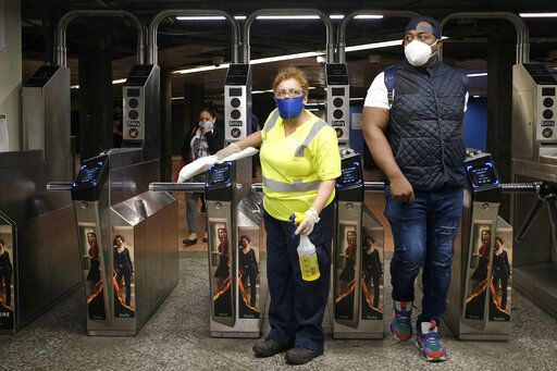An MTA employee cleans turnstiles as commuters pass through in New York, Monday, June 8, 2020. After three months of a coronavirus crisis followed by protests and unrest, New York City is trying to turn a page when a limited range of industries reopen Monday.