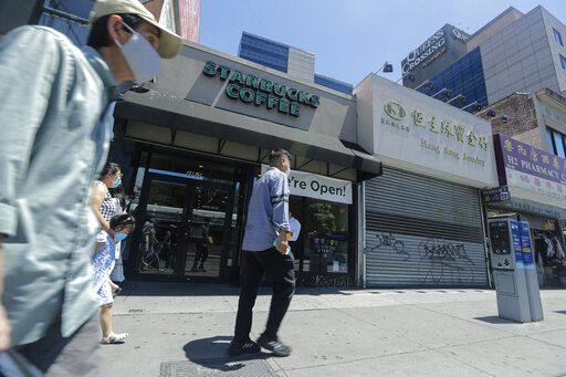 Patrons pass a Starbucks and a closed jewelry store Monday, June 8, 2020, in the Queens borough of New York. After three bleak months, New York City will try to turn a page when it begins reopening Monday after getting hit first by the coronavirus, then an outpouring of rage over racism and police brutality.