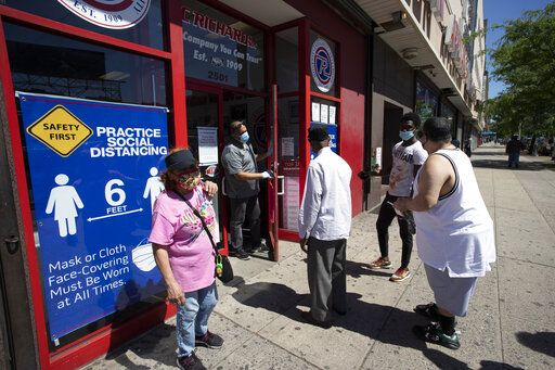 A store employee, second from left, talks to waiting customers at P.C. Richard and Son electronics and appliance store, Monday, June 8, 2020, in the Bronx borough of New York. The store is only providing pick-up orders on Monday. It will reopen its doors later in the week. After three bleak months, New York City will try to turn a page when it begins reopening Monday after getting hit first by the coronavirus, then an outpouring of rage over racism and police brutality.