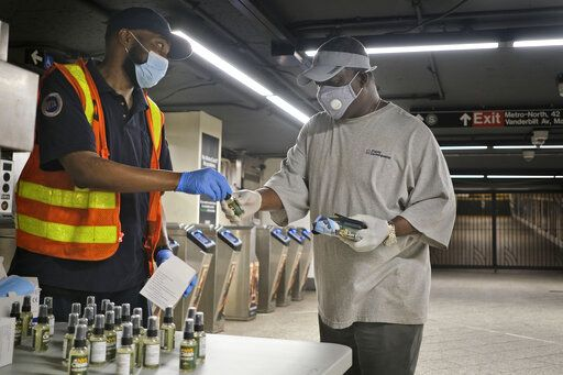 MTA employee Shawn Turner, left, gives away masks and hand sanitizer at the entrance to a subway station in New York, Monday, June 8, 2020. After three months of a coronavirus crisis followed by protests and unrest, New York City is trying to turn a page when a limited range of industries reopen Monday.