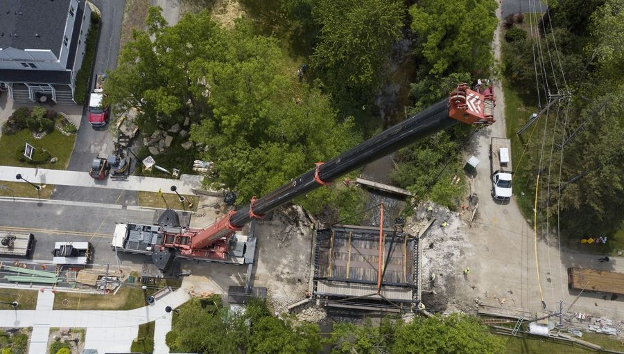 A massive crane lifts the approximately 40,000-pound Robert Parker Coffin Road bridge into place Tuesday in Long Grove. The bridge was removed in March to accommodate renovations to the abutments and other work. Work on the bridge will be completed after a new wooden cover is installed.