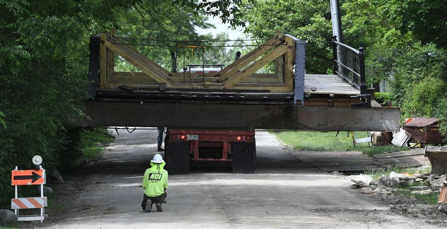 Workers from Alliance Contractors Inc. in Woodstock place downtown Long Grove's 114-year-old bridge back over Buffalo Creek. The crews skillfully avoided telephone poles and mailboxes.