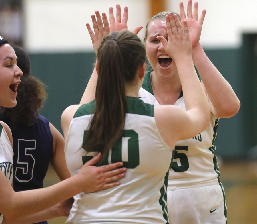 Glenbard West senior Taylor Huff, right, gets revved up with teammates during a game against Addison Trail at Biester Gymnasium on the campus of Glenbard West High School.