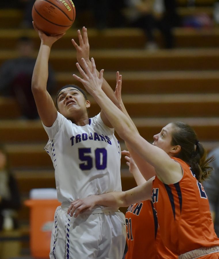 Downers Grove North's Alexis Parker gets around Naperville North's Kaitlyn Castillo and Sarah Crossett to score in a girls basketball game.