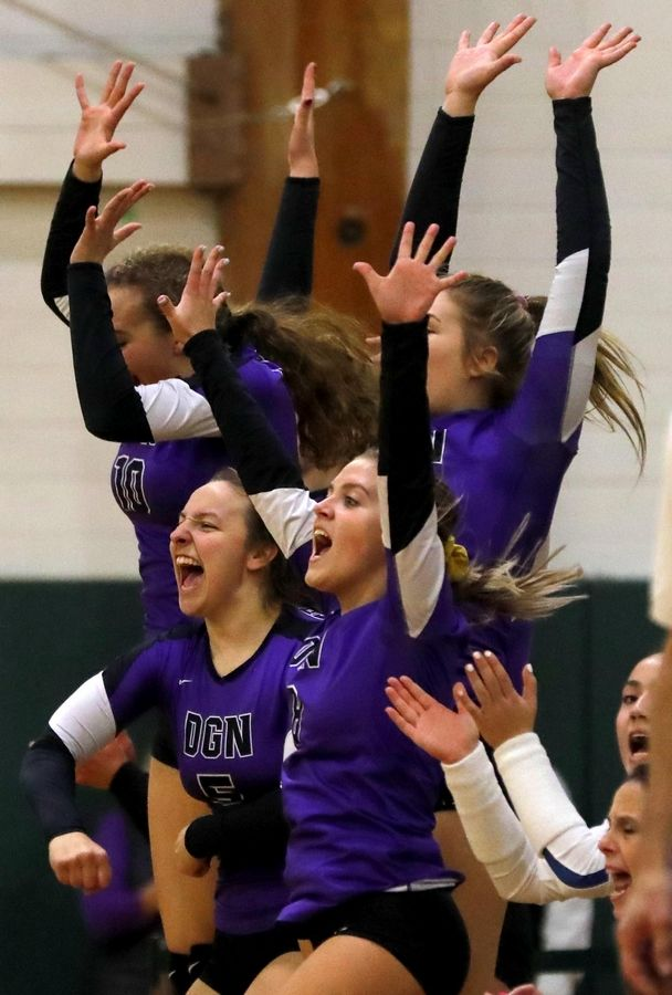Downers Grove North players cheer a point during a sectional volleyball game. At right is senior Aleks Glowik.