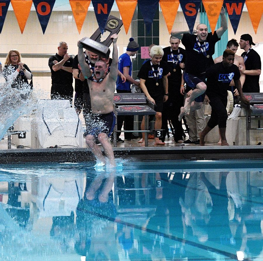 St. Charles North's Srboljub Filipovic jumps into the pool as he holds the state championship trophy at the IHSA state boys swimming finals.