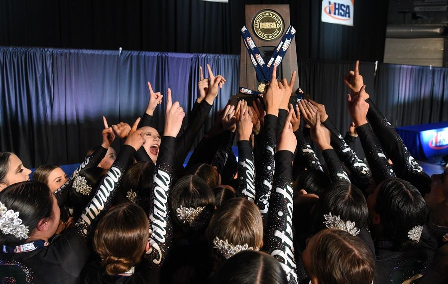 Stevenson High School dancers hold up their IHSA Class 3A state championship trophy at Grossinger Motors Arena in Bloomington.