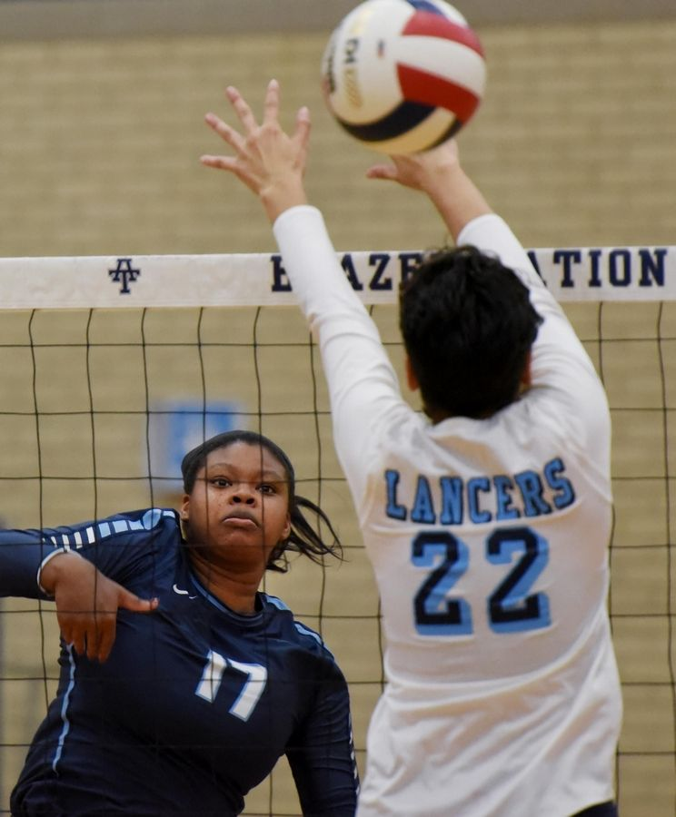 Downers Grove South's Jayla Hampton hits against Lake Park's Destiny Fisk in a regional semifinal girls volleyball match.