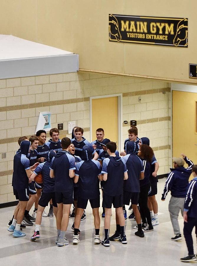 The Downers Grove South boys varsity basketball team chants together before entering the Metea Valley gymnasium for a game.