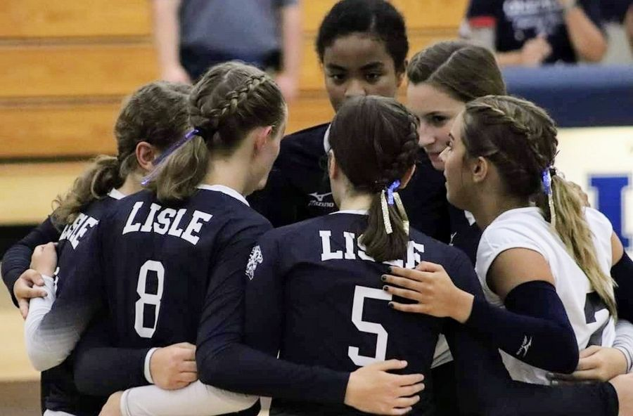 Lisle High School volleyball players huddle up during a game.