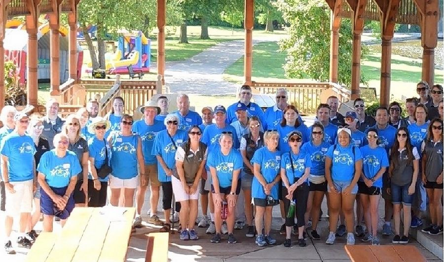 "Just before the arrival of nearly 1,000 children last July, many of the Kiwanis volunteers, including family and friends, took a group photo in the Pottawatomie Park Pavilion. The ""Day in the Park"" was spent playing games, eating ice cream, and making friends."
