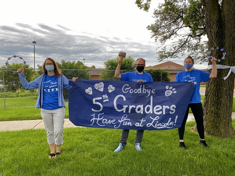 Lions Park Elementary School teachers wave goodbye to their fifth-grade students during the school's clapout on June 3.