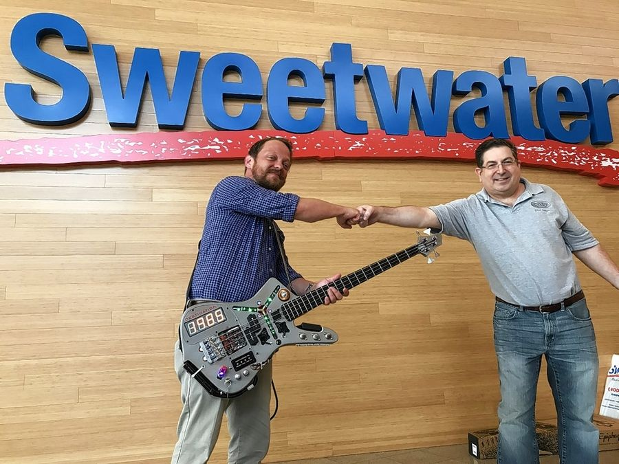"Sealing the deal with a COVID-19-conscious fist bump, Steve Doner, right, of Wheaton, sees his bass guitar inspired by the movie ""Back to the Future"" go to buyer Arend Raby at the Sweetwater Sound music store in Fort Wayne, Indiana."