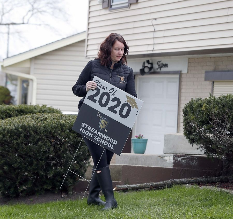 Streamwood High School Principal Jennifer Van Deusen and 80 volunteers deliver yard signs to seniors' homes in April.
