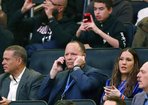 FILE - In this March 2, 2020, file photo, New York Knicks president Leon Rose, center, takes a phone call during the first quarter of an NBA basketball game against the Houston Rockets in New York. Rose didn't have much time to evaluate the Knicks after becoming team president in March. But with their season officially over, he can begin making changes after another losing season.