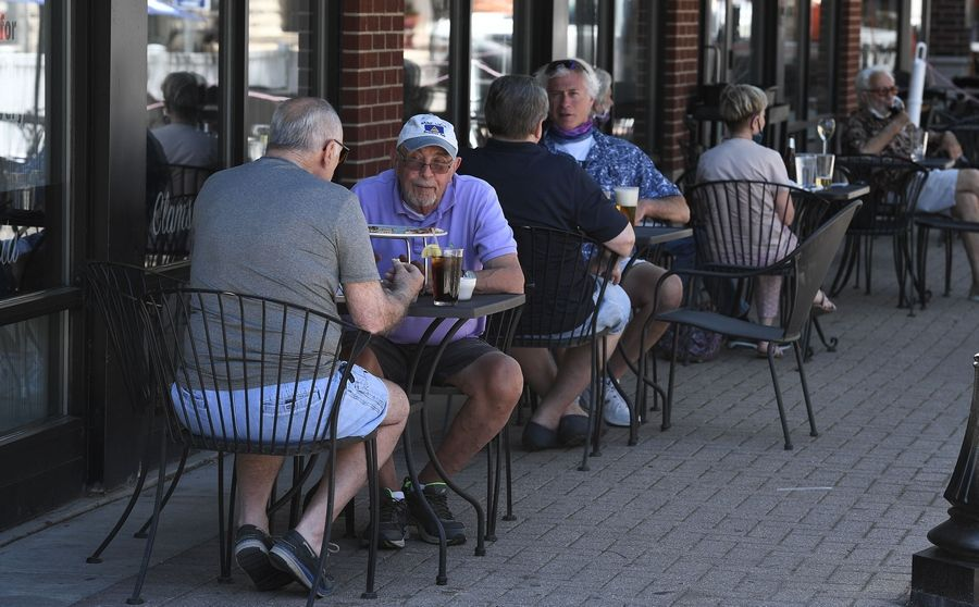 Customers relax while social distancing and wearing masks during lunch hour in downtown Arlington Heights. Keeping 6 feet apart as required by state guidelines proves challenging when seated at a small table like these patrons.