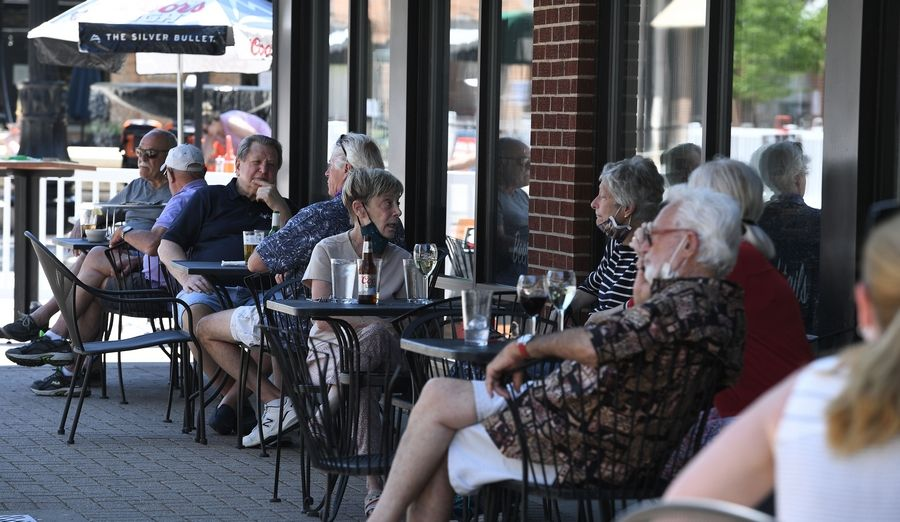 Patrons are spaced for social distancing but are close to one another because they are seated at small tables in the outdoor eating area in downtown Arlington Heights.