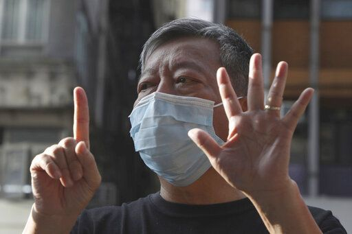 "FILE - In this May 1, 2020, file photo, pro-democracy activist Lee Cheuk-Yan displays opened palm with five fingers, signifying the ""Five demands - not one less,"" also representing ""May Day"" outside a shopping mall during the Labor Day in Hong Kong amid an outbreak of the new coronavirus. Video app company Zoom said Thursday, June 11 2020, it regretted that some meetings involving U.S.-based Chinese dissidents were disrupted, as meanwhile a prominent Hong Kong activist said his account was blocked despite the city's guarantees of free speech. Lee said he has been locked out of his paid Zoom account."