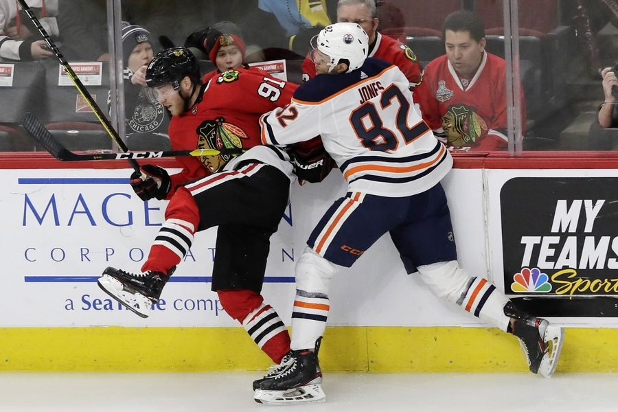 Blackhawks center Drake Caggiula is checked by Edmonton defenseman Caleb Jones in the first period of the March 5 game at the United Center. The Hawks beat the Oilers 4-3