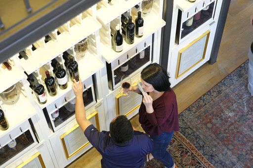 People tastes wines from a dispensary at the Oakville Wine Merchant Friday, June 12, 2020, in Oakville, Calif. California wineries started uncorking their bottles and welcoming people back to their tasting rooms Friday as the state's $145 billion tourism industry gears up with hotels, zoos, museums and aquariums also allowed to reopen. The wine retail experience in Oakville features 50 different wines by the taste or glass and is open to the public without an appointment.