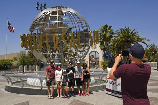 A family has their picture taken at Universal CityWalk, Thursday, June 11, 2020, near Universal City, Calif. The tourist attraction, which had been closed due to the coronavirus outbreak recently re-opened. The Universal Studios tour is still closed.
