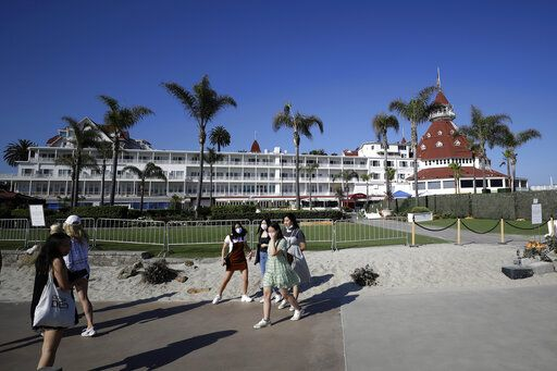 People pass the closed Hotel Del Coronado Thursday, June 11, 2020, in Coronado, Calif. California's tourism industry is gearing back up with the state giving counties the green light to allow hotels, zoos, aquariums, wine tasting rooms and museums to reopen Friday.