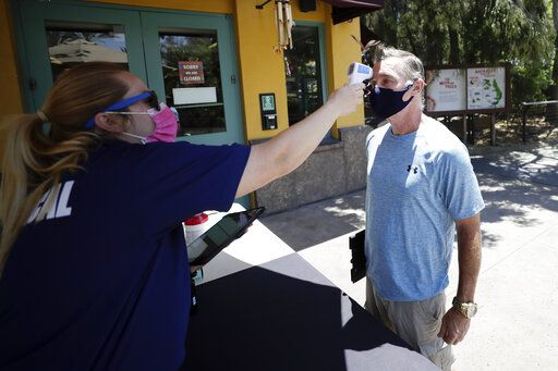 Health services worker Summer Deibert, left, checks the temperature of James McCluskey, right, as he arrives for work before the reopening of the San Diego Zoo, Thursday, June 11, 2020, in San Diego. California's tourism industry is gearing back up with the state giving counties the green light to allow hotels, zoos, aquariums, wine tasting rooms and museums to reopen Friday.