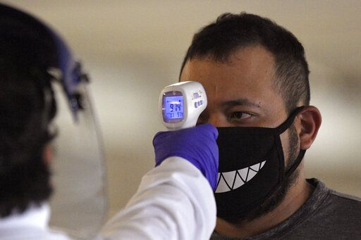Jose Ramirez has his temperature checked before entering Universal CityWalk, Thursday, June 11, 2020, near Universal City, Calif. The tourist attraction, which had been closed due to the coronavirus outbreak recently re-opened. The Universal Studios tour is still closed.
