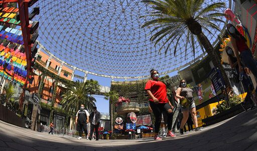 People walk through Universal CityWalk, Thursday, June 11, 2020, near Universal City, Calif. The tourist attraction, which had been closed due to the coronavirus outbreak recently re-opened. The Universal Studios tour is still closed.