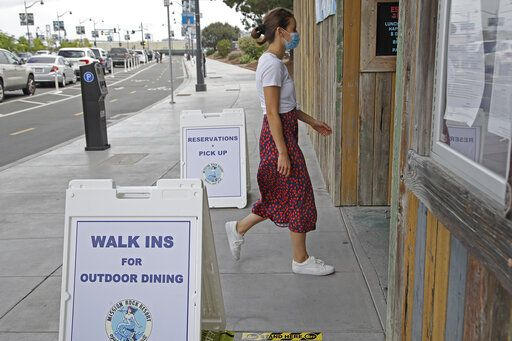 A woman walks into the Mission Rock restaurant on Friday, June 12, 2020, in San Francisco. Today was the first day outdoor dining is allowed in San Francisco restaurants.