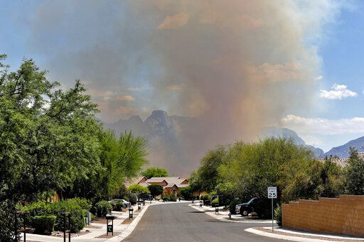 The Bighorn Fire backdrops a community along the western side of the Santa Catalina Mountains, Friday, June 12, 2020, in Tucson Ariz. Hundreds of homes on the outskirts of Tucson remain under an evacuation notice as firefighters work to keep the wildfire from moving downhill from canyons and ridges in the Coronado National Forest.