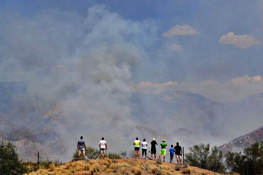 People watch wildfire air attack crews battle the Bighorn Fire along the western side of the Santa Catalina Mountains, Friday, June 12, 2020, in Oro Valley, Ariz. Hundreds of homes on the outskirts of Tucson remain under an evacuation notice as firefighters work to keep the wildfire from moving downhill from canyons and ridges in the Coronado National Forest.