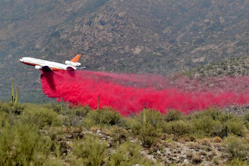 Heat ripples distort an air tanker as it drops retardant on the Bighorn Fire along the western side of the Santa Catalina Mountains, Friday, June 12, 2020, in Oro Valley, Ariz. Hundreds of homes on the outskirts of Tucson remain under an evacuation notice as firefighters work to keep the wildfire from moving downhill from canyons and ridges in the Coronado National Forest.
