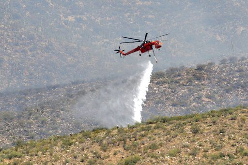 Heat ripples distort an air attack crew as they drop water on the Bighorn Fire along the western side of the Santa Catalina Mountains, Friday, June 12, 2020, in Oro Valley, Ariz. Hundreds of homes on the outskirts of Tucson remain under an evacuation notice as firefighters work to keep the wildfire from moving downhill from canyons and ridges in the Coronado National Forest.