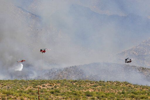 Wildfire air attack crews continue to battle the Bighorn Fire along the western side of the Santa Catalina Mountains, Friday, June 12, 2020, in Oro Valley, Ariz. Hundreds of homes on the outskirts of Tucson remain under an evacuation notice as firefighters work to keep the wildfire from moving downhill from canyons and ridges in the Coronado National Forest.