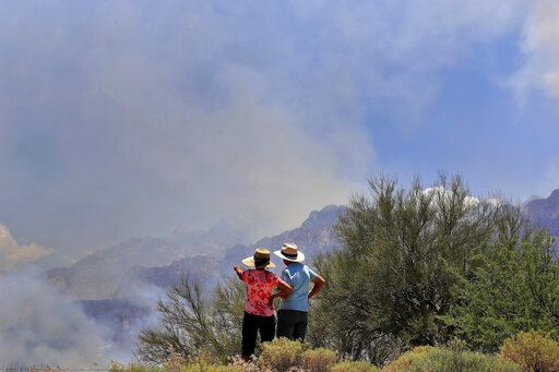A couple watches the Bighorn Fire burn along the northwestern side of the Santa Catalina Mountains, Friday, June 12, 2020, in Oro Valley, Ariz. Hundreds of homes on the outskirts of Tucson remain under an evacuation notice as firefighters work to keep the wildfire from moving downhill from canyons and ridges in the Coronado National Forest.