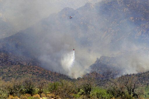 Wildfire air attack crews continue to battle the Bighorn Fire along the northwestern side of the Santa Catalina Mountains, Friday, June 12, 2020, in Oro Valley, Ariz. Hundreds of homes on the outskirts of Tucson remain under an evacuation notice as firefighters work to keep the wildfire from moving downhill from canyons and ridges in the Coronado National Forest.