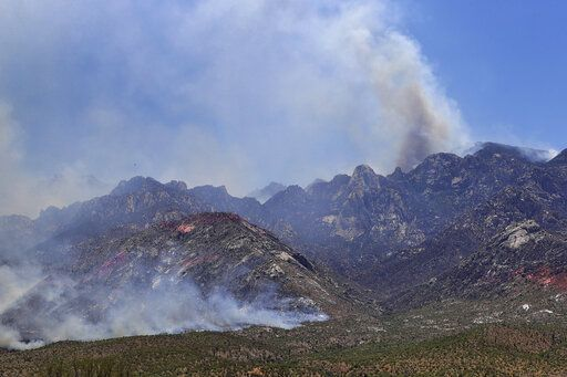 The Bighorn Fire burns along the northwestern side of the Santa Catalina Mountains, Friday, June 12, 2020, in Oro Valley, Ariz. Hundreds of homes on the outskirts of Tucson remain under an evacuation notice as firefighters work to keep the wildfire from moving downhill from canyons and ridges in the Coronado National Forest.