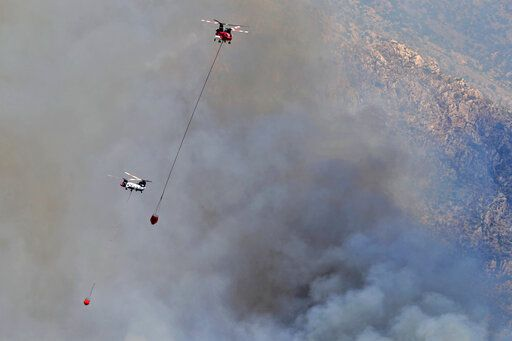 Wildfire air attack helicopters continue to battle the Bighorn Fire along the western side of the Santa Catalina Mountains, Friday, June 12, 2020, in Oro Valley, Ariz. Hundreds of homes on the outskirts of Tucson remain under an evacuation notice as firefighters work to keep the wildfire from moving downhill from canyons and ridges in the Coronado National Forest.