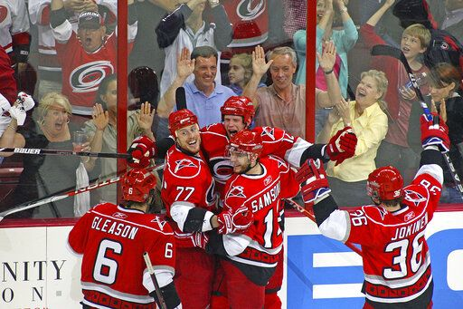 FILE - In this May 8, 2009, file photo, then-Carolina Hurricanes' Eric Staal, center, celebrates his goal against the Boston Bruins with teammates Joe Corvo (77), Sergei Samsonov, second from right, of Russia, Jussi Jokinen (36), of Finland, and Tim Gleason (6) during the third period of Game 4 of an NHL hockey Eastern Conference semifinal series in Raleigh, N.C. When the virus risk wanes enough to allow the games to begin again, the very essence of these events will be missing for at least awhile. 'œSure, it would still be guys competing at their highest level and their hardest, because that's what we do,'� said Minnesota Wild center Eric Staal. 'œBut as far as comparing it to a full building in a Game 7,  there's no comparison.'�