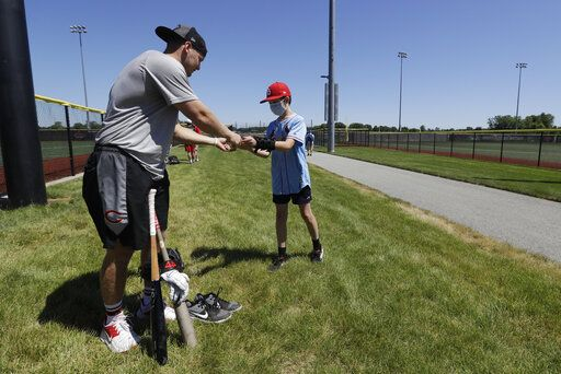 Cincinnati Reds' Josh VanMeter signs an autograph for Sam Berry following a workout at Grand Park, Friday, June 12, 2020, in Westfield, Ind. Proceeds from the event will go to Reviving Baseball in the Inner City of Indianapolis.
