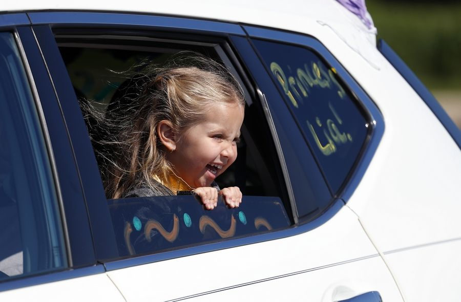 Three-year-old Princess Lia Mendez of Streamwood peaks excitedly out of her window during the drive-through Character Parade in the parking lot of the Sears Centre Arena in Hoffman Estates Saturday.