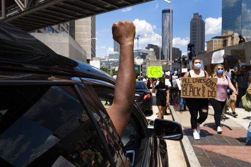 Protesters get support from a passengers of a cars they march past CNN during a demonstration over the death of Floyd, Saturday, June 13, 2020 in Atlanta. (John Amis/Atlanta Journal-Constitution via AP)