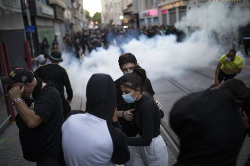 Protesters react to tear gas fired by French riot police during a march against police brutality and racism in Marseille, France, Saturday, June 13, 2020, organized by supporters of Adama Traore, who died in police custody in 2016 in circumstances that remain unclear despite four years of back-and-forth autopsies. Several demonstrations went ahead Saturday inspired by the Black Lives Matter movement in the U.S.